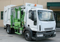 Side-loader waste collection vehicle