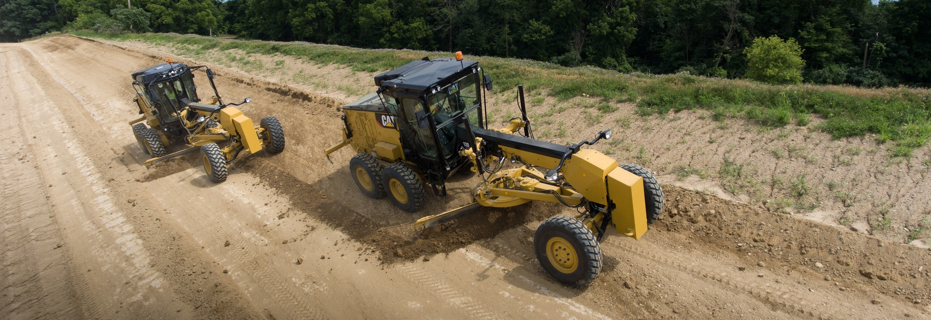 The Cat 120 motor grader has two different cab styles, one for wheel/lever controls (right) and another for the joystick controls (left).