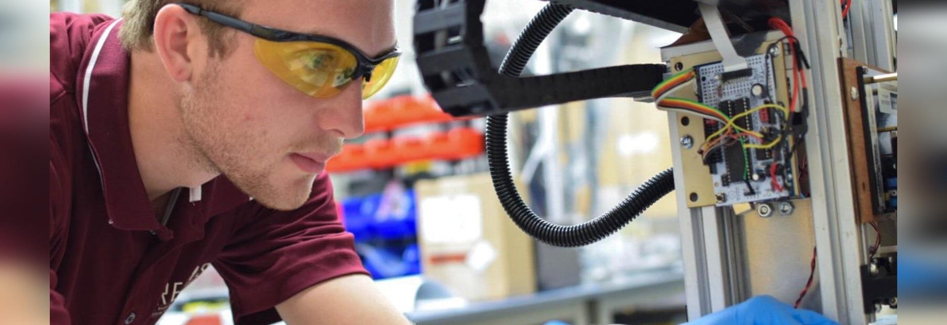 Daniel Rau works with a 3D printer in the DREAMS Lab.