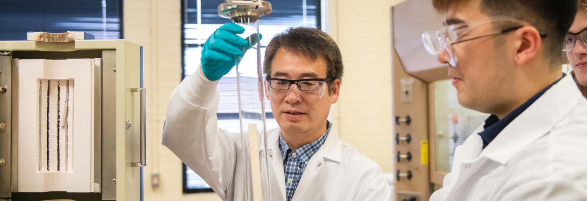 "Jianhua ""Joshua"" Tong, left, and Ph.D. student Shenglong Mu work in their Sirrine Hall lab"