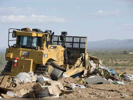 A Caterpillar D-8 dozer is shown working at a landfill, a demanding application used for testing an unconventional magnetic filter component in equipment's hydraulic system.