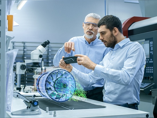 Two Engineers Works with Mobile Phone Using Augmented Reality Holographic Projection 3D Model of the Engine Turbine Prototype. Development of Virtual Mixed Reality Application.